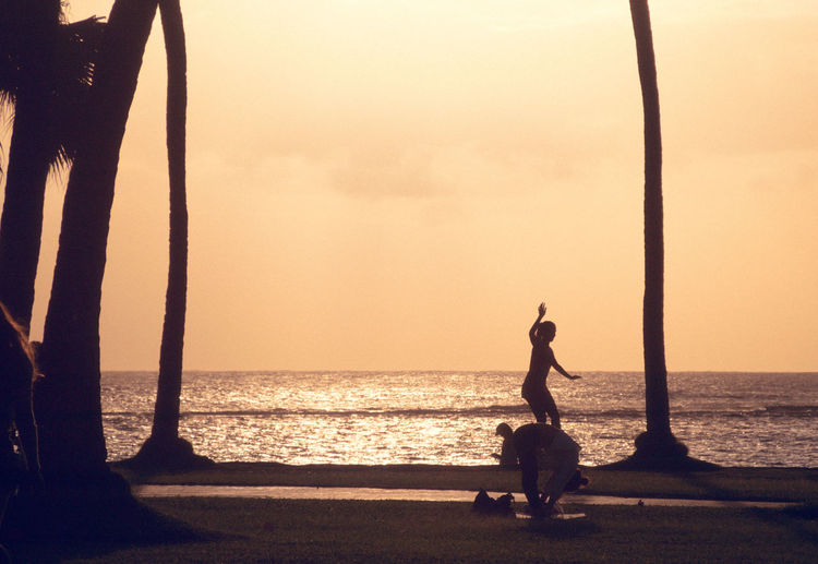 Silhouette of statue at beach during sunset