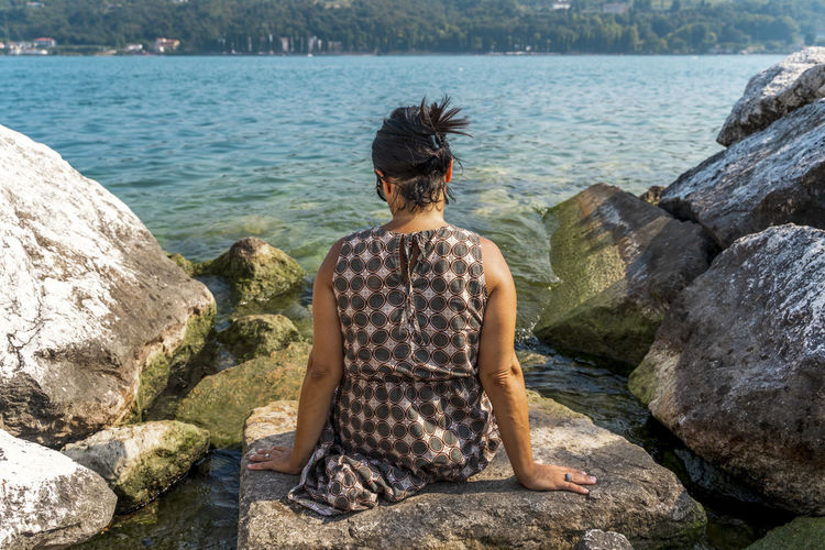 Rear view of woman looking at lake while sitting on rock
