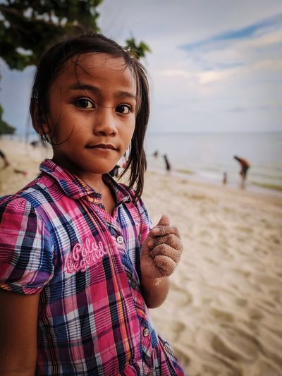 Portrait of cute girl standing at sandy beach
