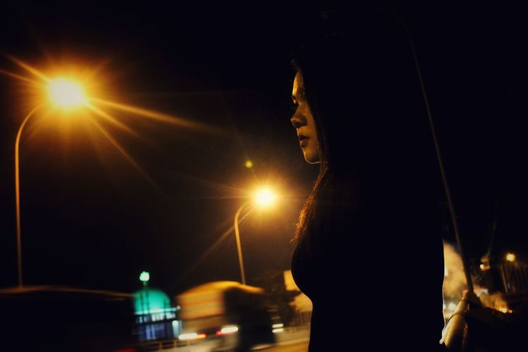 Woman standing in illuminated city against sky at night