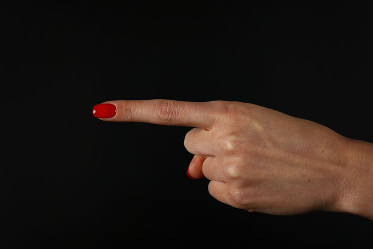 Woman hand shoing direction with pointing finger with red nail polish Copy Space Target Adult Black Background Blame Close-up Direct Direction Gesture Gesturing Human Body Part Human Finger Human Hand Index Finger Nail Polish One One Person People Pointing Pointing Finger Real People Red Studio Shot