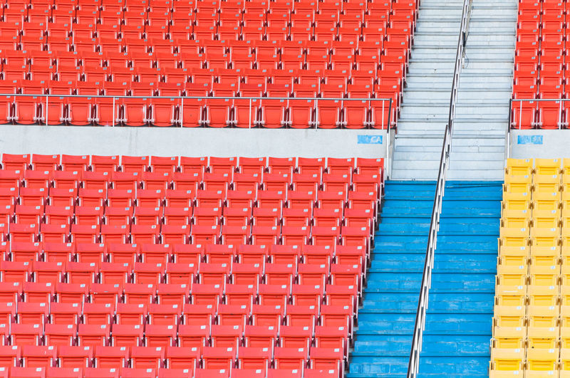 Empty orange and yellow seats at stadium,Rows of seat on a soccer stadium Bench Grandstand Horizontal Objects Orange Spectators Stadium Vacant Architecture Bleachers Building Exterior Chairs Color Empty Group Pattern Plastic Red Row Same  Seat Seats Sport Textured  Yellow