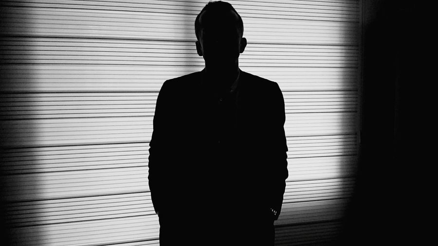 Silhouette businessman standing against blinds window