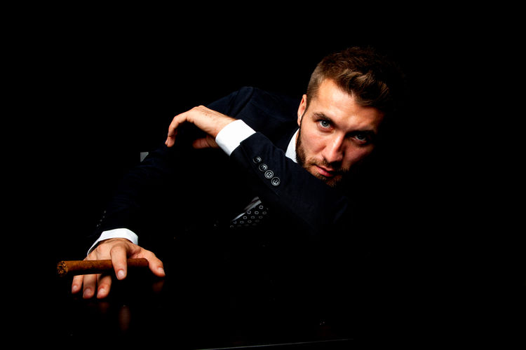 Attractive business man with a cigar Studio Shot One Person Black Background Portrait Indoors  Adult Men Cigarette  Cigar Smoke Smoking - Activity Suit Businessman Boss Manager Enjoyment Beard Bearded Handsome Elegant Successful Confident  Pensive Fashion Model