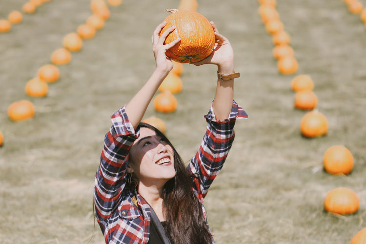 Smiling young woman holding pumpkin at agricultural field