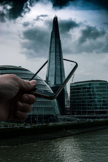 Digital Composite Image Of Cropped Hand Holding Mobile Phone Amidst Shard London Bridge