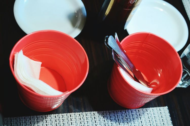 High angle view of silverware and tissue papers in red disposable glass on table