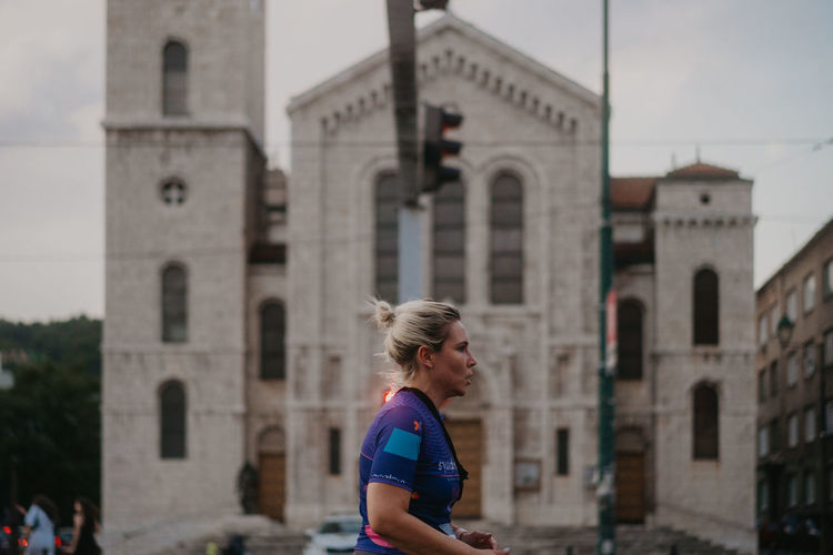 Side view of woman standing against building in city