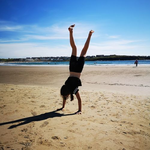 Full length of girl doing handstand on sand against sea at beach