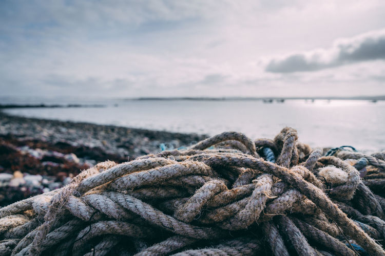 Close-up of rope tied to bollard on sea shore