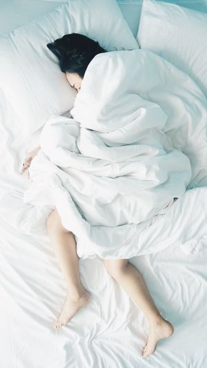 High angle view of person sleeping in bed