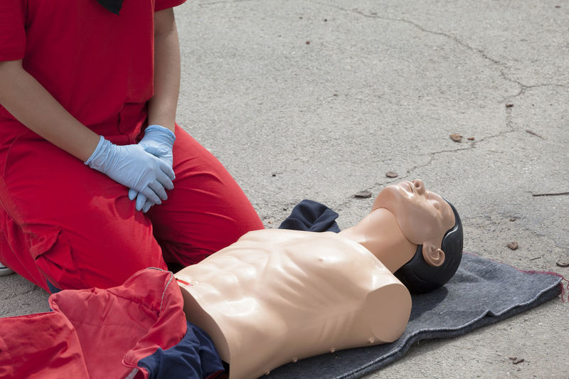 Midsection of woman by cpr dummy