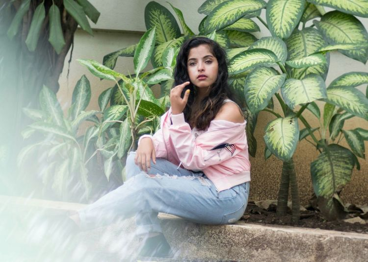 Portrait Of A Young Woman Sitting Against Plants