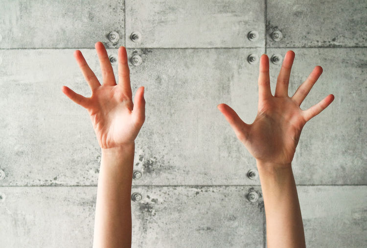 Cropped Image Of Hands Against Wall