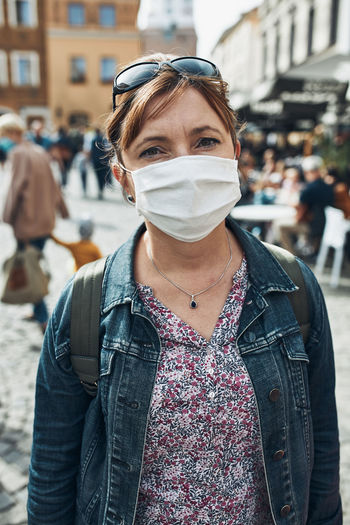 Portrait of woman wearing mask standing on street