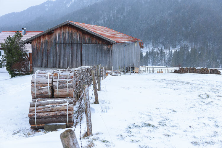 Firewood on a barn in snowy bavarian landscape in snowfall and mountain forest in the background.
