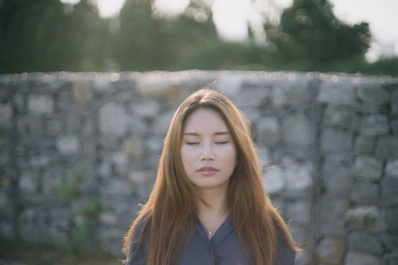 Young woman with eyes closed standing against stone wall
