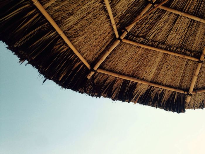 Low angle view of thatched roof against sky during sunny day