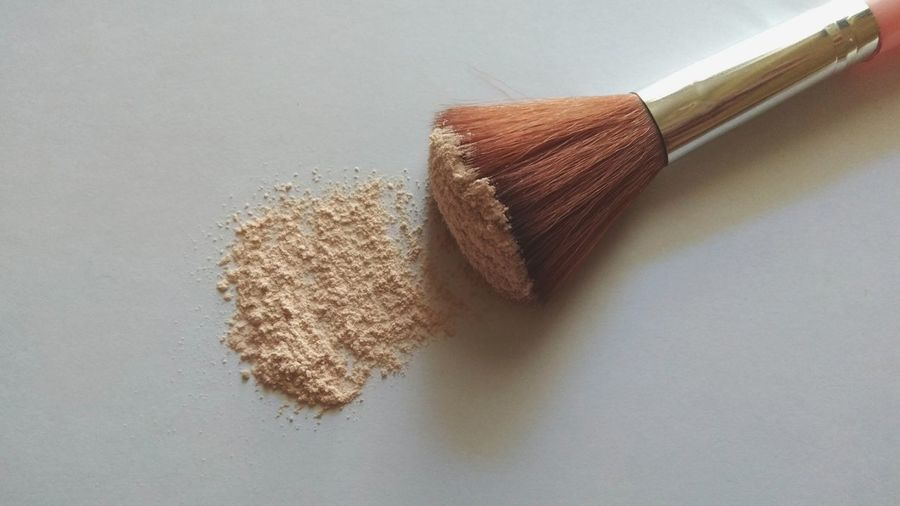 High angle view of make -up brush and powder on table