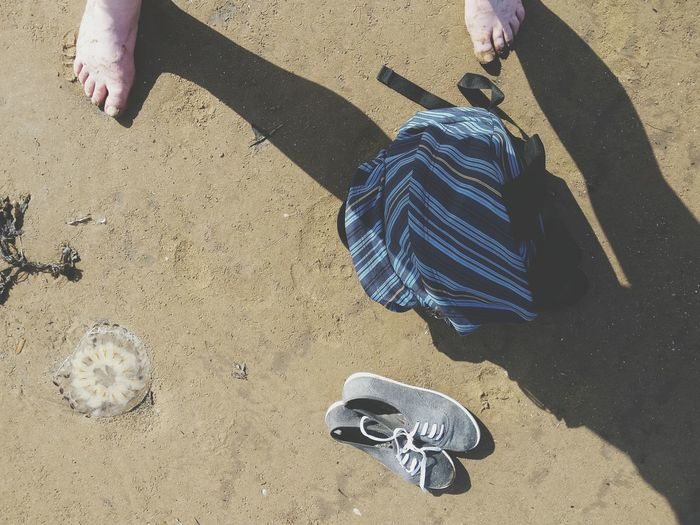 Low section of person standing by bag and shoes on beach during sunny day