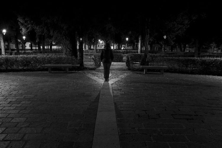 Rear view of man walking on footpath at night