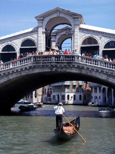 Man in gondola at grand canal with people standing on rialto bridge