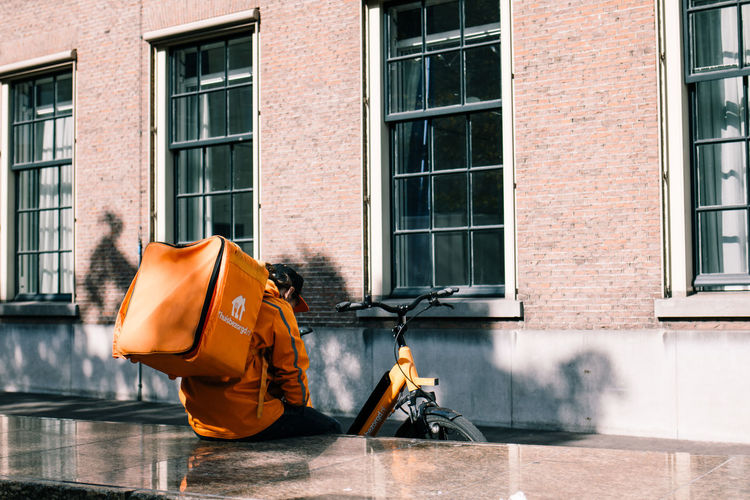 Delivery Orange Architecture Backpack Bag Brick Building Building Exterior Built Structure City Day Food Glass - Material Job Lifestyles Men Motion One Person Orange Color Outdoors Real People Reflection Street Thuisbezorgd Window