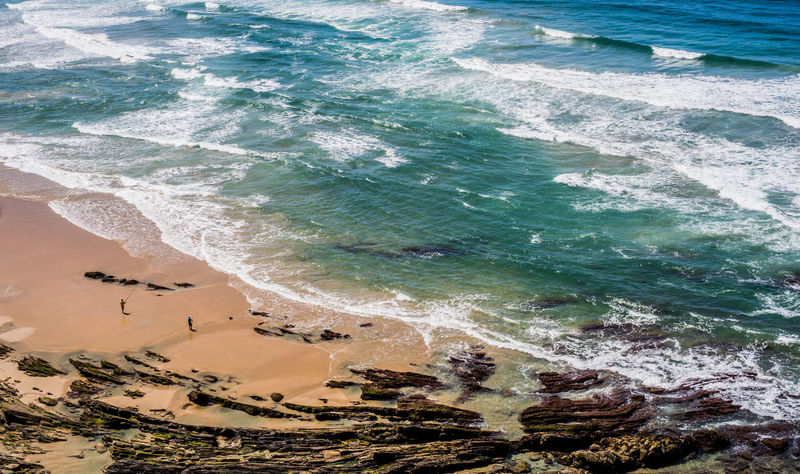 Aquatic Sport Beach Beauty In Nature Day High Angle View Land Motion Nature Outdoors Power In Nature Rock Sand Scenics - Nature Sea Sport Surfing Turquoise Colored Water Wave
