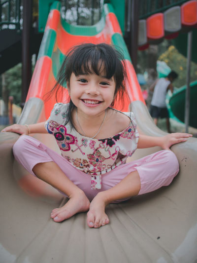 Cute little asian girl having smile on slide Child Real People Girls Sitting Front View Women Smiling Full Length Females One Person Innocence Emotion Lifestyles Happiness Childhood Cute Leisure Activity