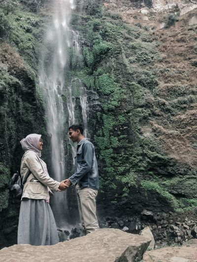 Couple holding hands while standing against waterfall
