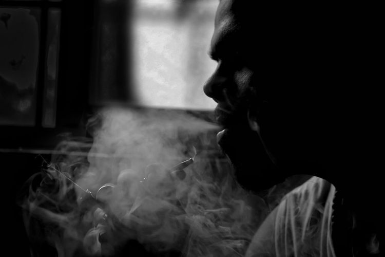 Side view of man smoking cigarette