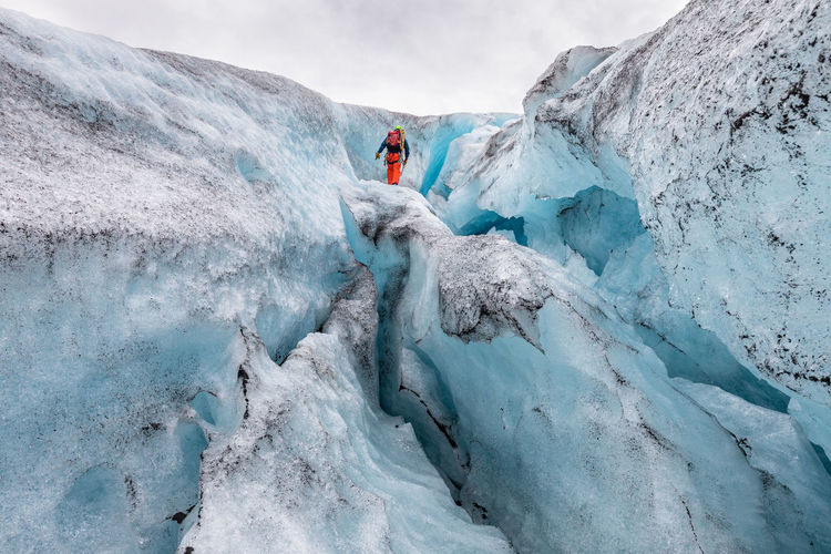 Low Angle View Of Hiker Standing On Snow Formation