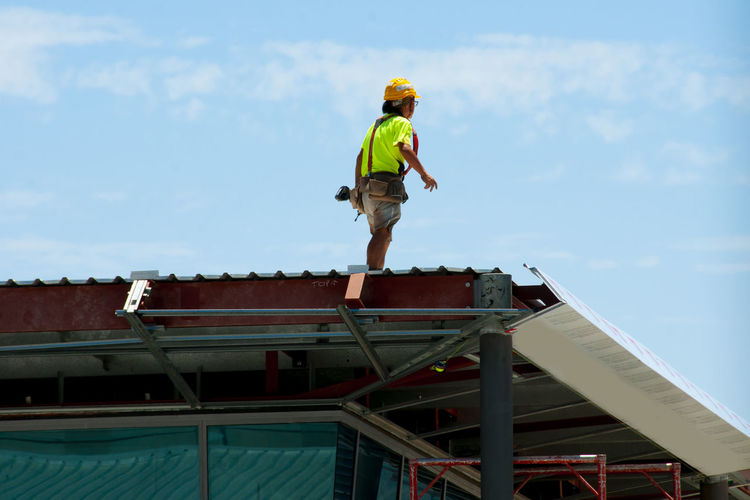 Low angle view of boy standing on roof against sky