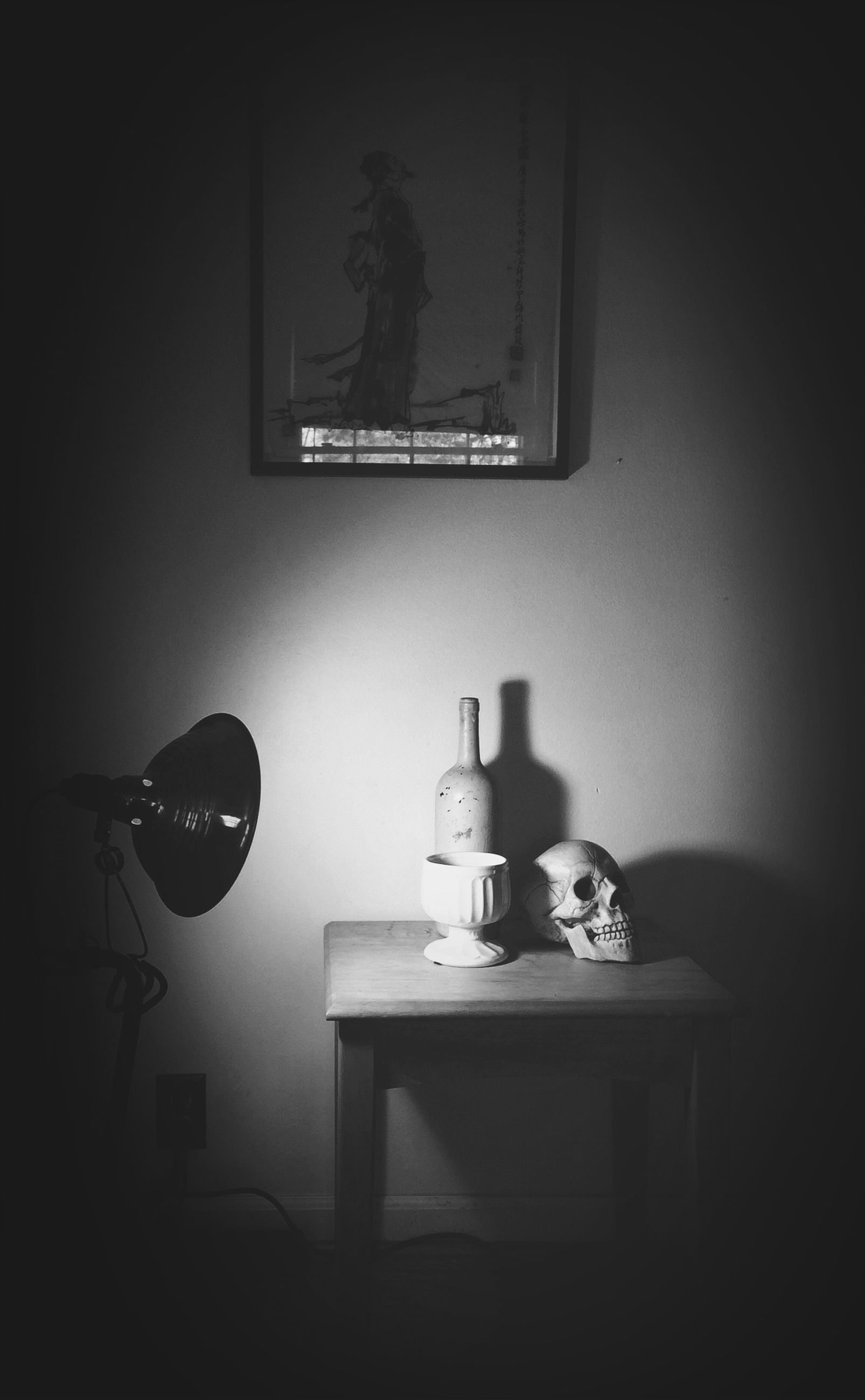 indoors, home interior, table, domestic room, wall - building feature, still life, electric lamp, domestic life, home, picture frame, house, room, lighting equipment, window, illuminated, copy space, technology, no people, chair, darkroom