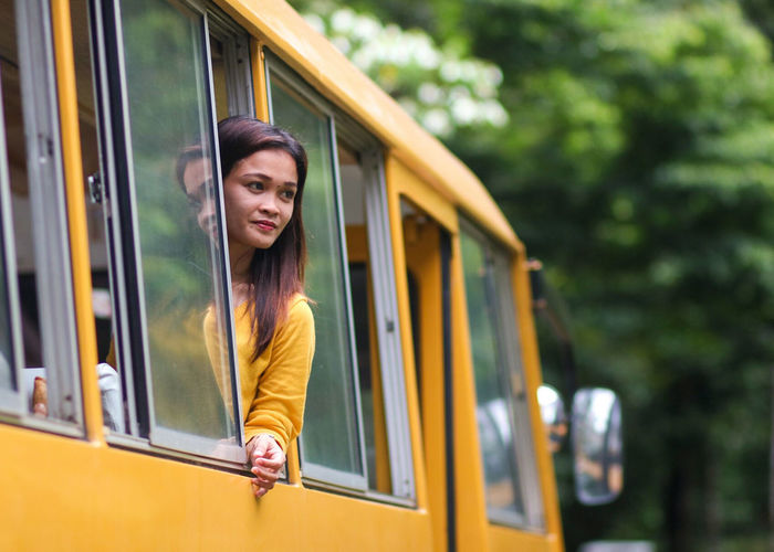 woman in the bus Adventures In The City Out Of The Town Travel Woman In The Bus Yellowl Yellow Bus  Young Woman Peaking Through The Window Riding A Bus Travel City Young Women Hailing Yellow Taxi Women Portrait Cheerful Happiness Car Door Smiling This Is My Skin The Portraitist - 2018 EyeEm Awards
