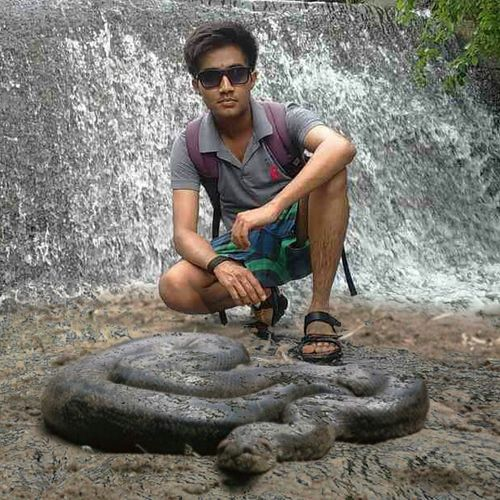 Ramesh Gore, Anaconda, Waterfall, Fearless, Fearlessness Editing Full Length Person Sitting Casual Clothing Looking At Camera Portrait Lifestyles Young Adult Leisure Activity Crouching Confidence  Front View Mature Adult Outdoors In Front Of