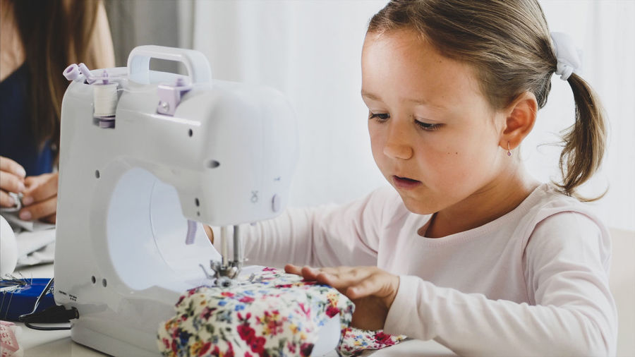 Close-up of cute girl sewing textile at home