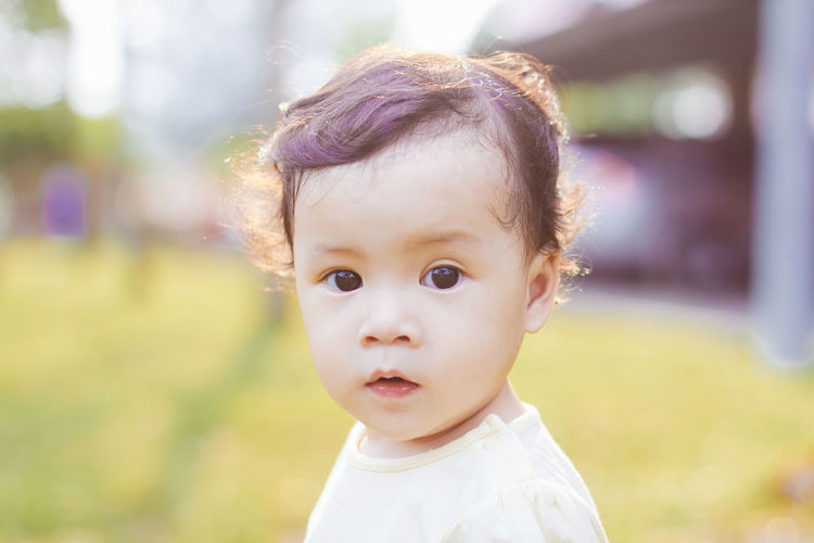 Close-up portrait of cute baby girl at park