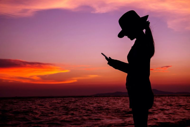 Silhouette of woman text messaging on mobile phone at seaside during sunset