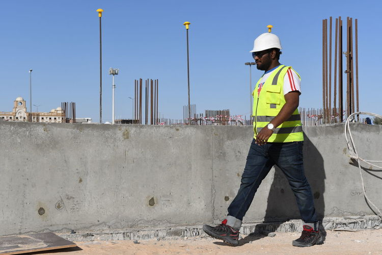 Man holding blueprints while walking at construction site