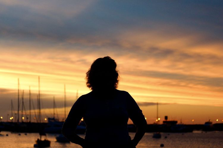 Silhouette woman standing against moored boats on lake during sunset