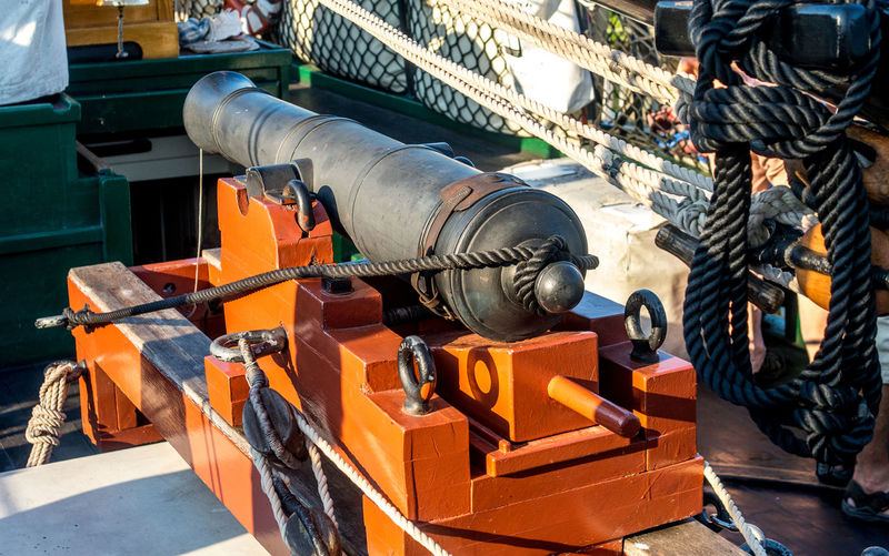 A 6 lb cannon is mounted on the deck of a 1810 wooden tall ship