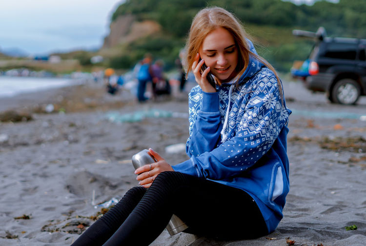 Young woman talking on mobile phone while sitting at beach
