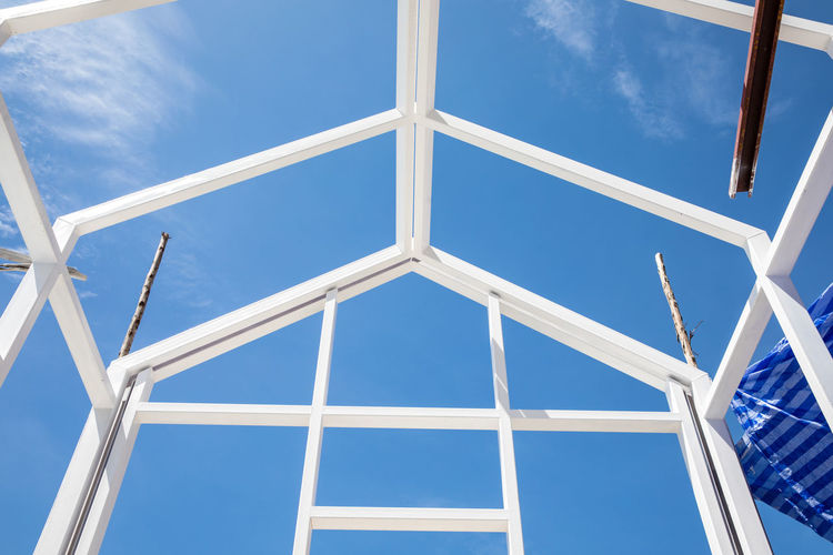 New house construction with white steel frame structure, blue sky