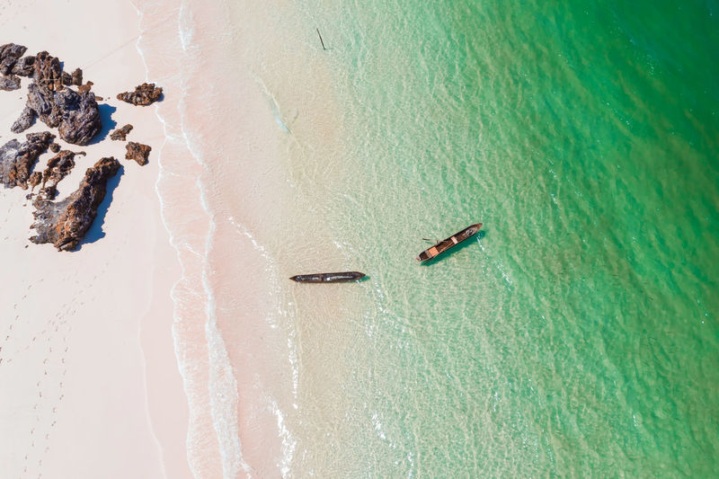 High angle view of empty canoes floating on water at beach