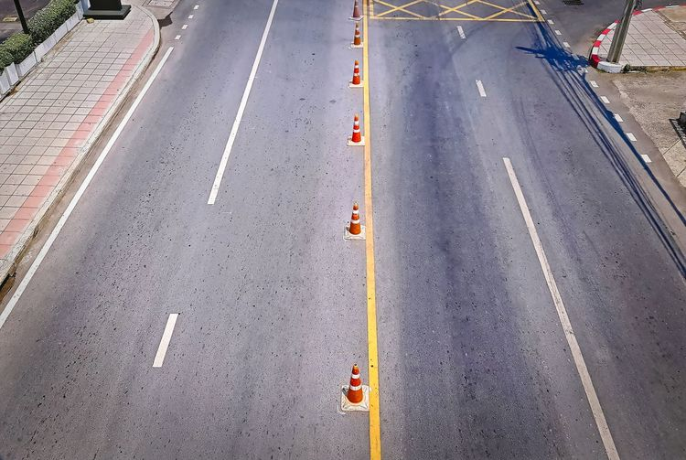 Road with Orange Plastic Traffic Cones Traffic Asphalt City Cone Day Direction Dividing Line Guidance High Angle View Marking Mode Of Transportation No People Outdoors Road Road Marking Sign Street Symbol The Way Forward Transportation Travel