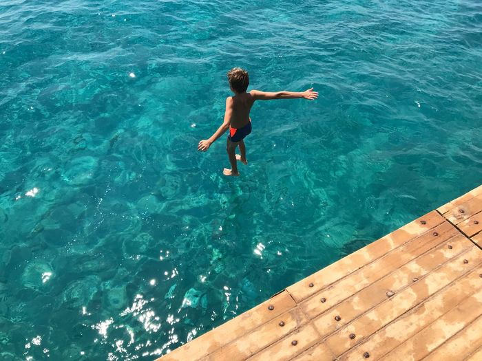 High angle view of shirtless boy jumping in sea
