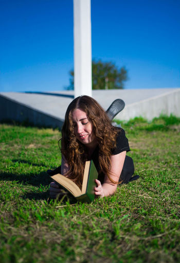 Young woman reading book on field against sky