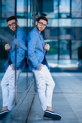 Business Business Person Businessman Communication Confidence  Eyeglasses  Full Length Happiness Lifestyles Looking At Camera Men Mobile Phone Outdoors Portrait Professional Occupation Real People Smiling Sunglasses Technology Wireless Technology Young Adult Young Men