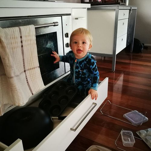 Baby Boy Looking Away While Sitting In Drawer Of Cabinet In Kitchen At Home